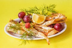 Plate with sliced smoked salmon with herbs,grapes and lemon Stock Photos