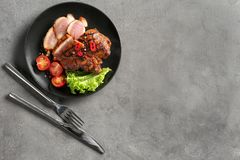 Plate with sliced tasty steak and vegetables on table stock photo