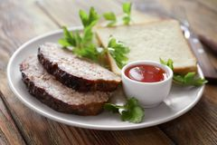 Plate with sliced tasty turkey meatloaf. On table royalty free stock images
