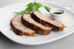 Plate with sliced tasty turkey meatloaf. On table stock photos