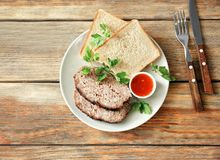 Plate with sliced tasty turkey meatloaf. On table stock photography