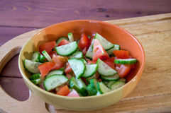 Plate with sliced vegetables. Salad from tomato and cucumber. On the cutting board Stock Photo