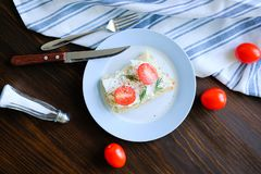 Plate with slices of bread or sandwiches with tomatoes, cheese and herbs on a wooden table. Next to a kitchen knife, a towel, salt royalty free stock photo