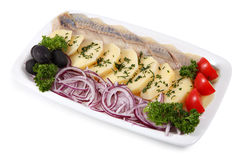 Plate with slices of pickled herring, onion, and boiled potatoes Royalty Free Stock Photography