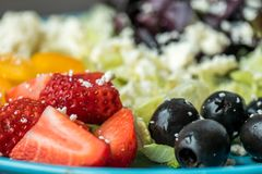 Plate of Slices of Strawberries and Green Leaf Vegetables stock photos