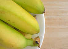 Plate of small bananas on a wood table Stock Photos