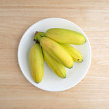 Plate of small bananas on a wood table Royalty Free Stock Photos
