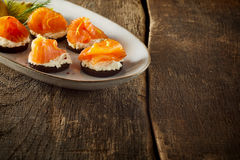 Plate of smoked salmon canapes on a rustic table. Plate of smoked salmon canapes on a rustic wooden table with irregular boards and copy space for your menu or Stock Images