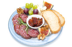 Plate of snacks - sausage, bread, figs, grapes, nuts, dried tomato Stock Photos