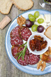 Plate of snacks - sausage, sun-dried tomatoes, nuts, fruit, cheese Royalty Free Stock Photos