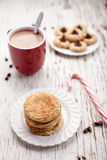 Plate of snickerdoodle cookies and hot chocolate on weathered white wood. Plate of snickerdoodle cookies, hot chocolate, peppermint candy cane, and chocolate Stock Photography