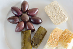 Plate with some food for fasting. Fasting food concept of plate with olives, dolma, halva and lagana stock images