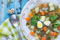 Plate with sorrel soup, quail eggs and spoon. Top view stock images