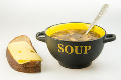 Plate with soup and bread. Mushroom soup in a bowl, bread, cheese. On a table on a white background Stock Photography