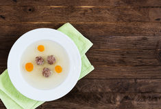 Plate of soup with carrot and meat balls on green Royalty Free Stock Images