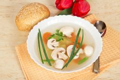 Plate with soup, spoon, bread and red tulips Stock Photography