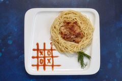 Plate with spaghetti and cutlet, tic-tac-toe sauce paint. Kids menu Royalty Free Stock Photography