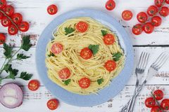 A plate with spaghetti with tomatoes. A plate full of pasta with tomatoes, onion and parsley stock photos