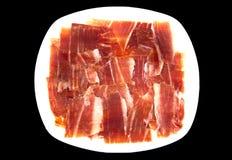 Plate of spanish serrano ham on black background. Royalty Free Stock Photo