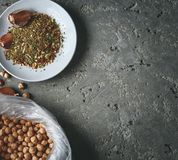 A plate of spices, chickpea and garlic on the grey concrete backdrop. A plate of spices, bag with chickpeas, chickpea and garlic on the grey concrete backdrop Royalty Free Stock Images