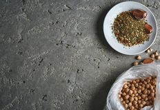 A plate of spices, chickpea and garlic on the grey concrete backdrop. A plate of spices, bag with chickpeas, chickpea and garlic on the grey concrete backdrop Stock Images
