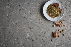 A plate of spices, chickpea and garlic on the grey concrete backdrop. Ingredients of hummus - Middle Eastern dish - chickpeas puree. Top view copy space Stock Photo