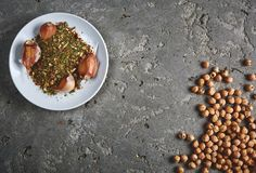 A plate of spices, chickpea and garlic on the grey concrete backdrop. Ingredients of hummus - Middle Eastern dish - chickpeas puree. Top view copy space Royalty Free Stock Photos