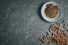 A plate of spices, chickpea and garlic on the grey concrete backdrop. Ingredients of hummus - Middle Eastern dish - chickpeas puree. Top view copy space Royalty Free Stock Photo