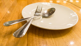 Plate, spoon and fork. Empty and clean plate, spoon and fork on a wooden food table in a restaurant Royalty Free Stock Photos