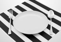 Plate with spoon and fork on a table Stock Photography