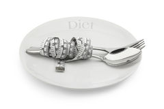 Plate with a spoon and fork wrapped in measuring tape Royalty Free Stock Photos