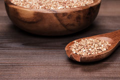 Plate and spoon full of buckwheat over wooden Royalty Free Stock Images