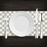 Plate with spoon, khife and fork on a wood table Royalty Free Stock Photo