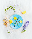 Plate with spring flowers, fork, sign and decoration on gray wooden background, top view Stock Images