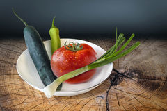 Spring Vegetables Set On Old Wooden Surface. Plateful of Spring Vegetables, fresh ripe Tomato, Cucumber, Spring Onion and Cayenne Pepper, placed on an old Stock Photography