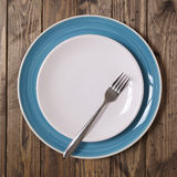 Plate stack. And fork on a wooden background Stock Photography