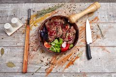 Authentic wooden plate with steak and vegetables and sauce. A plate with steak pieces and vegetables, poured with sauce and spices with a knife and appliance to Stock Image