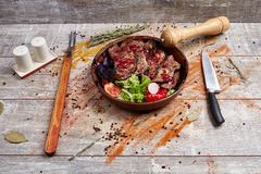 Authentic wooden plate with steak and vegetables and sauce. A plate with steak pieces and vegetables, poured with sauce and spices with a knife and appliance to Royalty Free Stock Photos
