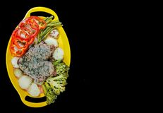 Plate of steak and vegetables on a yellow plate on a black background with space for text.  royalty free stock photo