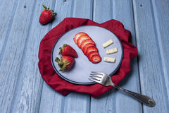 Plate of strawberries and cheese. Strawberries, sliced and whole, are on a plate with some cheese Stock Images
