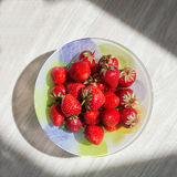 Plate with strawberries clouse up on a light blurred background. Stock Photo
