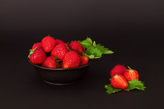 Plate of strawberries with leaves and cut strawberry Royalty Free Stock Photos