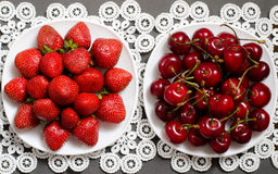 Plate with strawberries and a plate of red cherries on a lacy napkin, top view Royalty Free Stock Photography