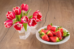 Plate of strawberries and tulips on wood Royalty Free Stock Photos