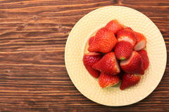 Plate of strawberries on a wooden background Royalty Free Stock Image