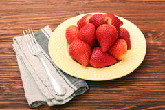 Plate of strawberries on a wooden background Royalty Free Stock Photography