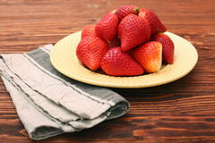 Plate of strawberries on a wooden background Royalty Free Stock Photos