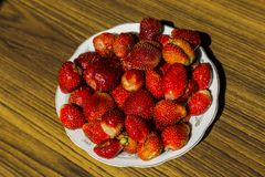 Plate with strawberries. On wooden table top view Stock Photography