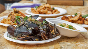 Plate with street food mussels and other dishes outdoor Stock Photo