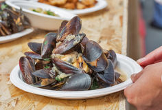 Plate with street food mussels and other dishes outdoor Royalty Free Stock Photography